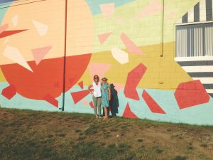 Artist Tessa O'Brien and Heather Seymour enjoy a proud moment together in front of one of the East Bayside Trail murals. Photo courtesy of the Portland Mural Initiative.